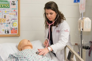 Montgomery County Community College student and Phi Theta Kappa Frank Lanza Memorial Scholarship recipient Kimberly Coffland works with a simulated mannequin in the College's Nursing Lab. Photo by Sandi Yanisko.